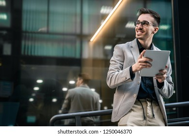 Smiling businessman using tablet outdoors