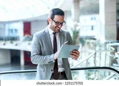 Smiling businessman using tablet for reading e-mail while standing near fence in business center.