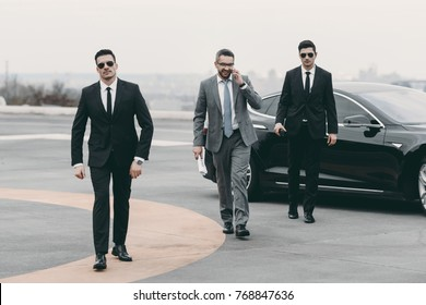 smiling businessman walking with bodyguards from car and talking by smartphone