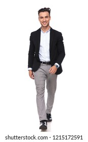 smiling businessman wearing black suit and grey pants steps forward on white background, full length picture