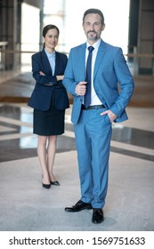Smiling businessman. Smiling businessman wearing elegant suit standing near his secretary after meeting
