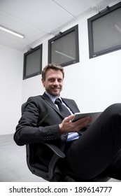 Smiling businessman at work holding a digital tablet with legs crossed.