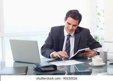 Smiling businessman working in his office