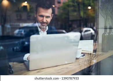 Smiling businessman working with laptop in modern cafe