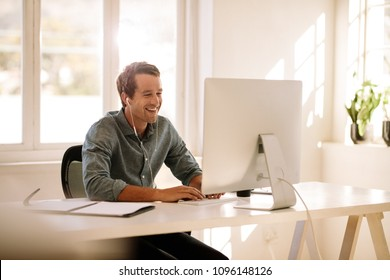 Smiling businessman working on computer. Man sitting at his work table working on computer at home listening to audio using earphones.