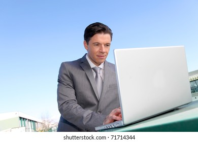 Smiling businessman working outside with laptop computer