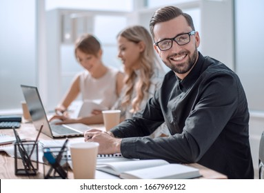 smiling businessman in the workplace in the office