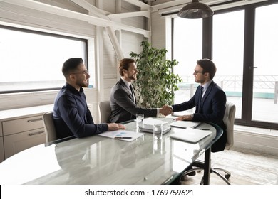 Smiling businessmen shake hands closing deal after successful negotiations in office, happy multiracial male business partners handshake get acquainted greeting at meeting, partnership concept