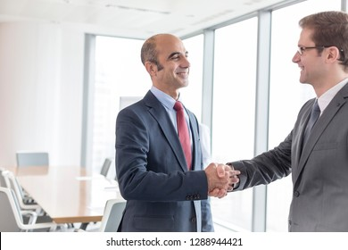 Smiling businessmen shaking hands while standing in boardroom during meeting at office