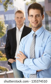 Smiling businessmen standing outside of office, looking at camera.