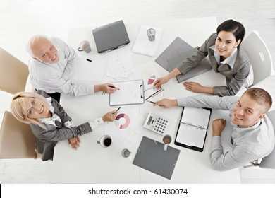 Smiling businesspeople sitting at meeting table, working, pointing at document, smiling at camera, high angle view.