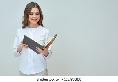 smiling businesswoman accountant wearing white shirt holding book. isolated studio portrait.