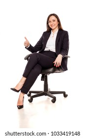 smiling businesswoman in armchair showing thumbs up on white background
