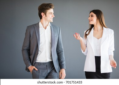 Smiling businesswoman and businessman are conversing against grey background.