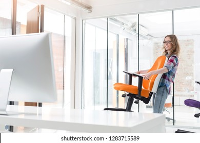 Smiling businesswoman carrying orange chair in new office