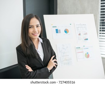 Smiling businesswoman crossed arm with chart background in office. Young Asian woman successful in small business