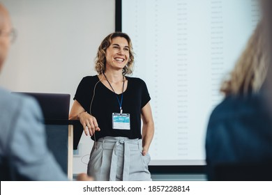 Smiling businesswoman delivering a speech during a conference. Successful business professional giving presentation. - Shutterstock ID 1857228814