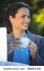 Smiling businesswoman drinking coffee with laptop in a restaurant