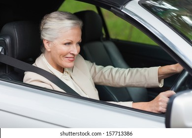 Smiling businesswoman driving classy car on a bright day