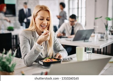Smiling businesswoman eating healthy food at work and having vegetable salad for lunch.