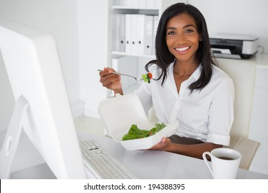 Smiling businesswoman eating a salad at her desk in her office
