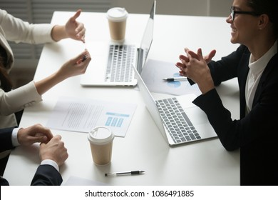 Smiling businesswoman enjoying talk to colleagues during teamwork with laptops, project team laughing working together at meeting, happy business people group have fun pleasant conversation in office
