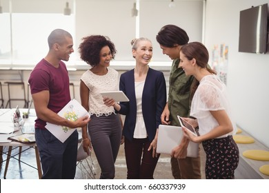 Smiling businesswoman explaining to creative team while holding tablet computer at office
