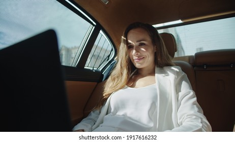 Smiling businesswoman getting good news on laptop computer in modern car. Happy business woman working on laptop in luxury car. Excited female ceo reading project in business car.