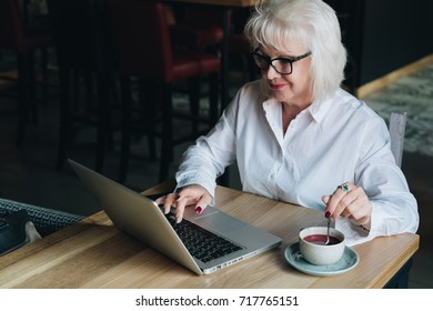 Smiling businesswoman in glasses sitting at table, working on laptop and drinking tea.Education for adults.Pensioner freelancer works.Woman is chatting, blogging, checking email.E-learning, startup.