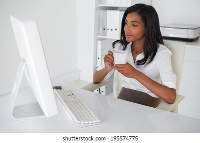 Smiling businesswoman having a coffee at her desk in her office