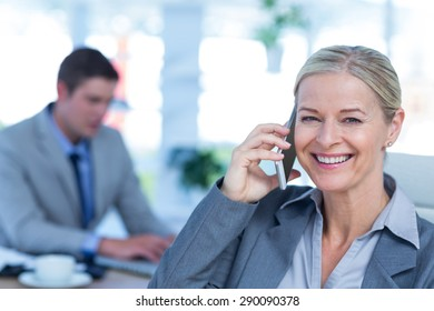 Smiling businesswoman having a phone call with colleague in background in an office