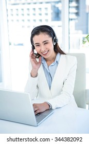 Smiling businesswoman with headset using laptop at the desk in work