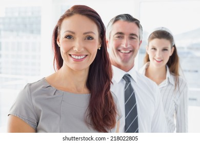Smiling businesswoman and her co-workers standing behind