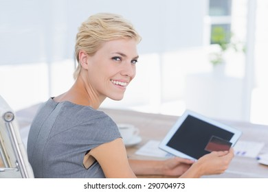 Smiling businesswoman holding credit card and tablet in her office