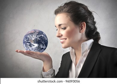 """Smiling businesswoman holding the Earth in her hand """"Elements of this image furnished by NASA"""""""