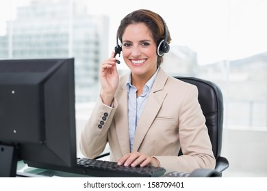 Smiling businesswoman holding headset in bright office