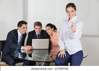 Smiling businesswoman holding her thumbs up with team in the background