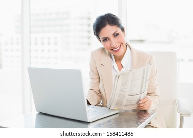 Smiling businesswoman holding newspaper while working on laptop at the office