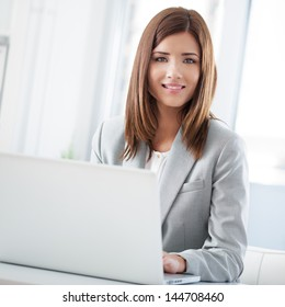 A smiling businesswoman holding a pen and posing for photographing.