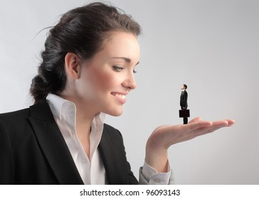 Smiling businesswoman holding a tiny businessman in her hand