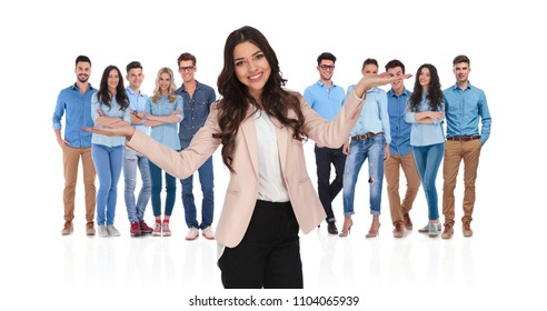 smiling businesswoman leader shrugging in front of the team with palms pointing up while standing on white background
