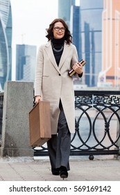 Smiling businesswoman in a light coat, with a briefcase and books in their hands walking along the embankment of the river against the background of skyscrapers in the business district