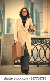 Smiling businesswoman in a light coat, with a case and books in hands walking along the quay of the river against the background of skyscrapers in business district. instagram image filter retro style