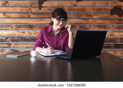 Smiling businesswoman listening to music as she works taking notes in a journal while reading from her laptop computer