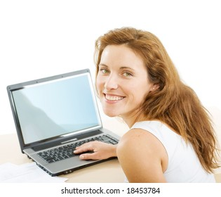 Smiling businesswoman looking at camera while touching keys of laptop near by