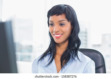 Smiling businesswoman looking at her computer in office