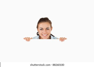 Smiling businesswoman looking over wall against a white background