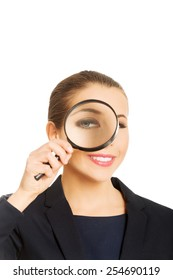 Smiling businesswoman looking through magnifying glass.