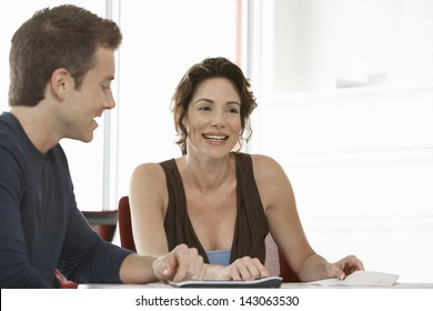 Smiling businesswoman with male colleague in meeting room