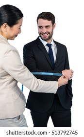 Smiling businesswoman measuring businessman sleeve against white background